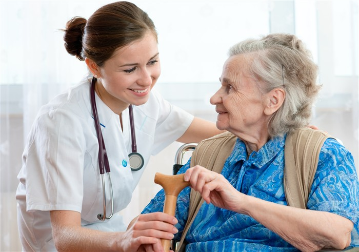 Personal support Worker handing her patient her cane
